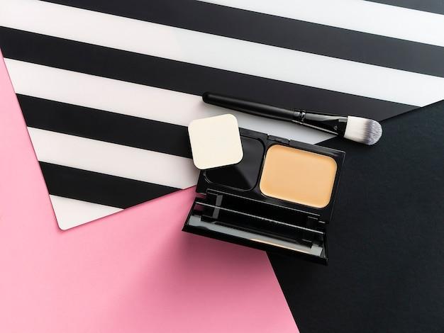 Kasten mit fester grundlage und spiegel, make-upapplikator auf rosa, weißem und schwarzem streifenhintergrund.