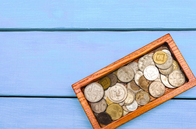 Kasten mit münzen der länder der welt auf einem blauen hölzernen hintergrund.