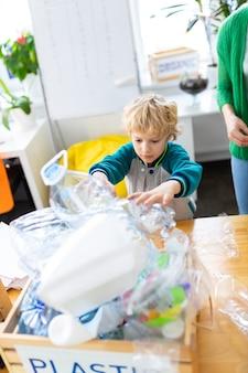 Kasten mit plastik. blonder hübscher schuljunge, der in der nähe einer kiste mit plastik steht, nachdem er abfall sortiert hat sort