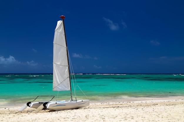 Katamaran an der küste des atlantischen ozeans mit einem hintergrund aus goldenem sand aus smaragdgrünem wasser und blauem himmel