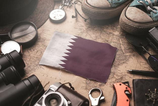 Katar-flagge zwischen dem zubehör des reisenden auf alter weinlese-karte. touristisches bestimmungsort-konzept.