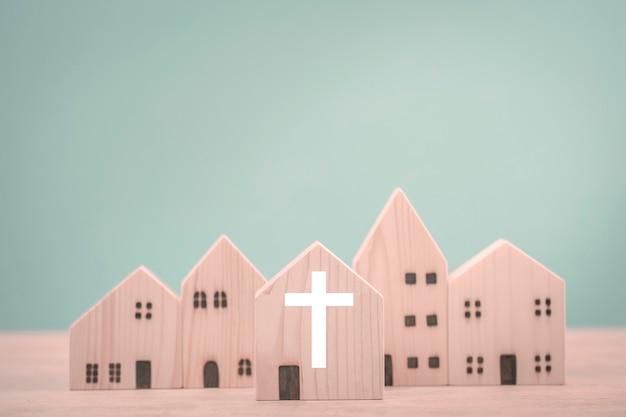 Katholische kirche und dorf aus holzhäusern auf neuwertigem hintergrund