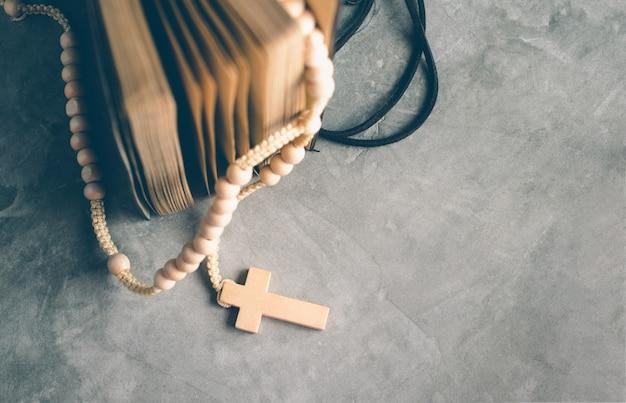 Katholische rosenkranzperlen mit altem buch auf zementtabellengebet, rosenbeethintergrundkonzept im weinleseton.