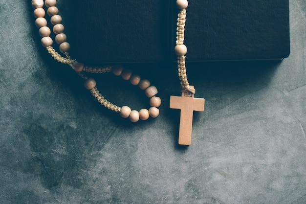 Katholische rosenkranzperlen mit altem buch auf zementtabellengebet, rosenkranz