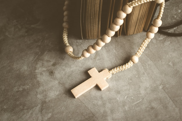 Katholische rosenkranzperlen mit altem buch auf zementtabellengebet, rosenkranzhintergrund im weinleseton.