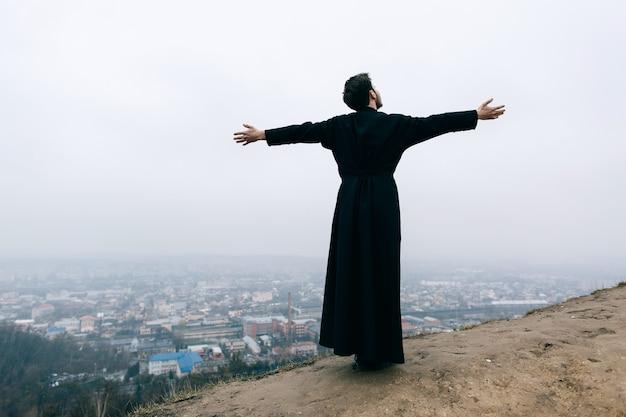 Katholischer bärtiger priester, der draußen in den bergen aufwirft