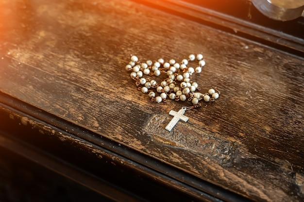 Katholisches kreuz in der kirche auf dem alten tisch.