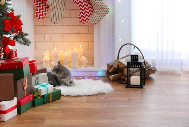 Katze, die nahe kamin im wohnzimmer liegt, das für weihnachten verziert wird