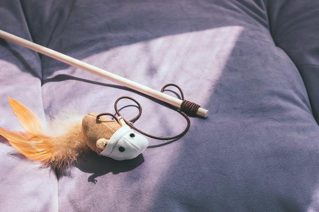 Katzenspielzeug teaser maus aus öko-materialien auf einem pastellfarbenen kissen oder bett