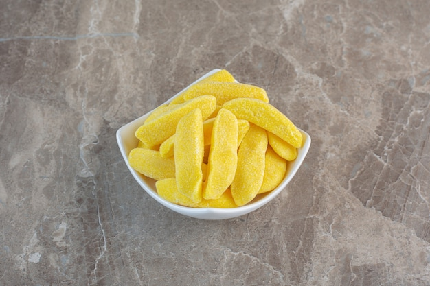 Kaubonbons der gelben frucht in der weißen schüssel über grauer oberfläche.