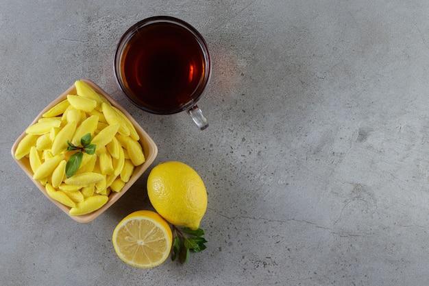 Kaubonbons in bananenform mit einer tasse heißem tee und frischer zitrone