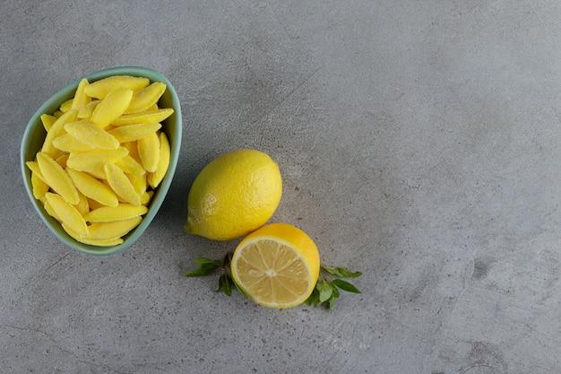 Kaubonbons in bananenform mit frischen zitronen- und minzblättern