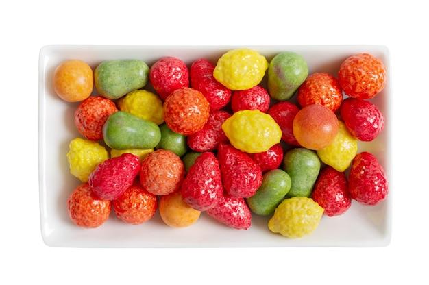 Kauen bunter kaugummi in form von früchten auf einem teller isoliert auf weißem hintergrund. die draufsicht