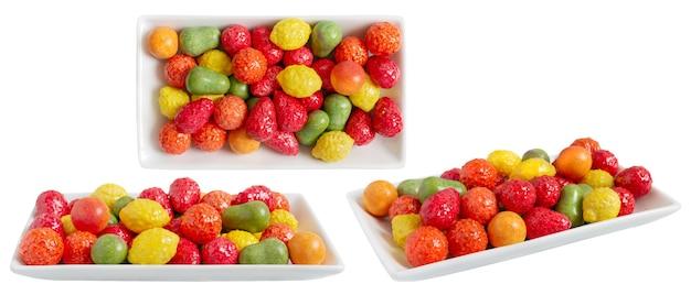 Kauen bunter kaugummi in form von früchten auf einem teller isoliert auf weißem hintergrund. verschiedene blickwinkel.