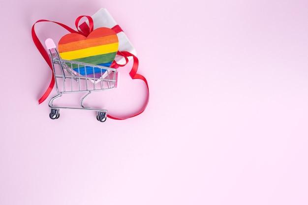 Kauf eines lgbt-geschenks für das valentinstagskonzept. geschenkbox mit rotem band und gemalter papier-lgbt-herzform im einkaufswagen auf rosa hintergrund