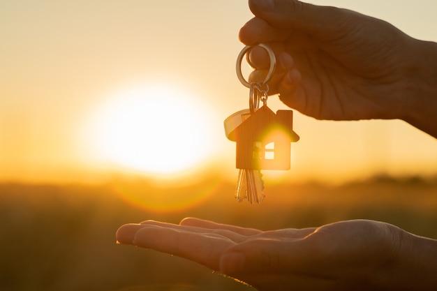Kauf oder miete eines wohnhauskonzepts eine frauenhand hält einen schlüssel mit einem schlüsselbund in form von ...