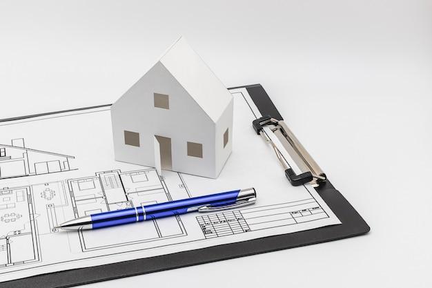 Kauf und verkauf von wohnungen. hypothek für den kauf eines hauses. mietgegenstand. ein mock-up eines papierhauses und eines kugelschreibers auf dem plan des zukünftigen hauses. nahansicht. platz kopieren. gutes geschäft.