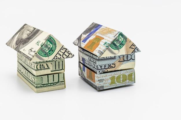 Kauf und verkauf von wohnungen. hypothek für den kauf eines hauses. mietgegenstand. häuser aus dollar-banknoten gefaltet. origami. nahansicht. platz kopieren. wohnen in den usa.