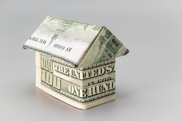 Kauf und verkauf von wohnungen. hypothek für den kauf eines hauses. mietgegenstand. haus aus dollar-banknoten gefaltet. origami. nahansicht. platz kopieren. wohnen in den usa.