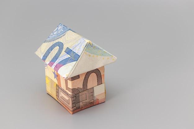 Kauf und verkauf von wohnungen. hypothek für den kauf eines hauses. mietgegenstand. haus aus euro-banknoten gefaltet. origami. nahansicht. platz kopieren. wohnen in europa.