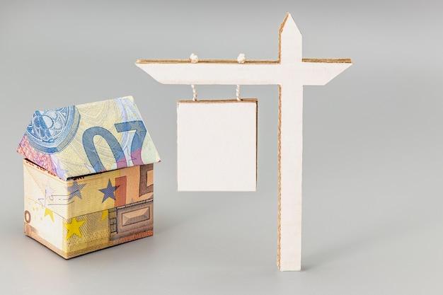 Kauf und verkauf von wohnungen. hypothek für den kauf eines hauses. mietgegenstand. haus gefaltet aus euro-banknoten mit einem schild zum verkauf oder zur vermietung. origami. nahansicht. platz kopieren.