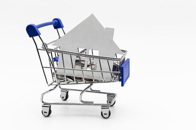 Kauf und verkauf von wohnungen. hypothek für den kauf eines hauses. mietgegenstand. mock-up eines papierhauses in einem münzladenwagen. nahansicht. platz kopieren. gutes geschäft.