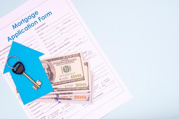 Kauf von immobilien, hypothekenzahlungskonzept. wohnung lag der schlüssel zu einer neuen wohnung oder einem neuen haus liegt auf einem fan von 100-dollar-scheinen für ein hypothekenantragsformular auf blauem hintergrund, kopierraum, draufsicht
