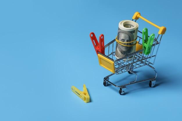 Kauf von wäscheklammern. farbige wäscheklammern an einer blauen wand, als substrat, stecknadel, wäscheklammer. viele bunte wäscheklammern an einer blauen wand. selektiver fokus