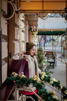 Kauf von waren und geschenken. einkaufen für die familie. weihnachtsverkaufskonzept. weibliches halten des weihnachtseinkaufstaschengeschenks. großer rabatt.