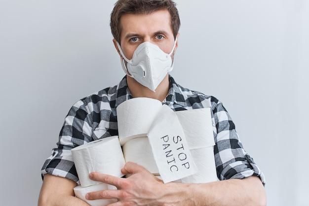 Kaufen sie aufgrund des coronavirus keine panik mehr für die quarantäne zu hause. bleiben sie zu hause für das schutzkonzept von covid-19. mann in der schutzmaske halten tissue-toilettenpapierrollen
