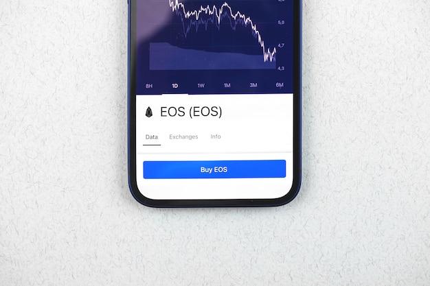 Kaufen sie eos-kryptowährung, handy-app mit schaltfläche, konzept des online-handels, investition und münzwechsel mit smartphone, finanzen, draufsichtfoto des schreibtisches