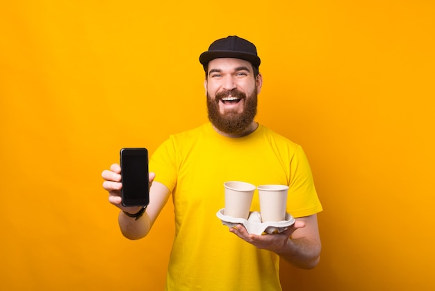 Kaufen sie kaffee online, mann zeigt smartphone und hält pappbecher kaffee auf gelb