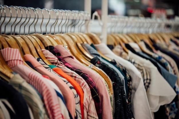 Kaufen sie kleidung, kleidershop auf kleiderbügel in der modernen boutique