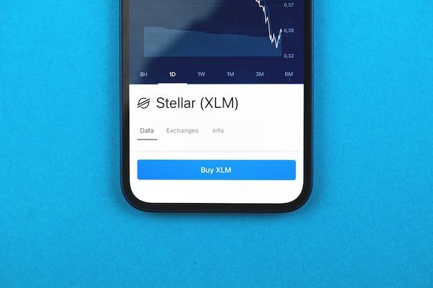 Kaufen sie stellar xlm-kryptowährung, handy-app mit schaltfläche, konzept des online-handels, investition und austausch mit smartphone, foto von oben auf dem schreibtisch des geschäftsbüros
