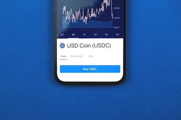 Kaufen sie usd-münze usdc-kryptowährung, handy-app mit schaltfläche, konzept des online-handels, investition und austausch mit smartphone, foto von oben auf dem schreibtisch des geschäftsbüros