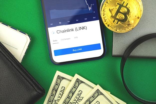 Kaufen und verkaufen sie chainlink link-kryptowährung mit ihrem mobiltelefon, mobiles banking-konzept mit neuem virtuellem geld, business-hintergrundfoto von oben