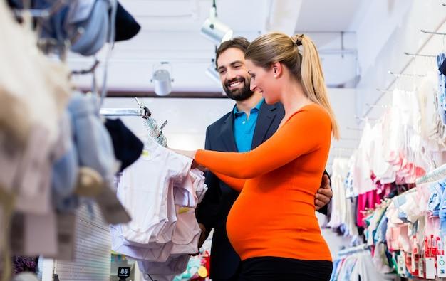 Kaufende babykleidung der schwangeren frau und des mannes im speicher