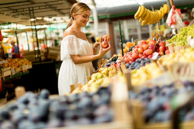 Kaufende früchte der jungen frau auf dem markt