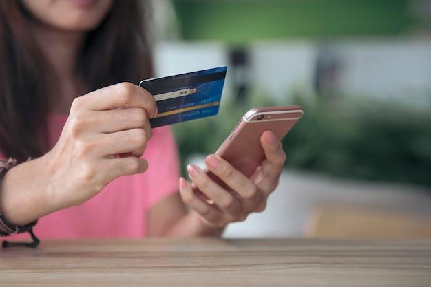 Kaufende online-zahlung mit kreditkarte, frau, die mobilen smartphone, geschäftse-commerce und anwendungskonzept verwendet