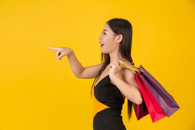 Kaufende schöne frau, die eine bunte papiertüte auf einem gelb anhält.