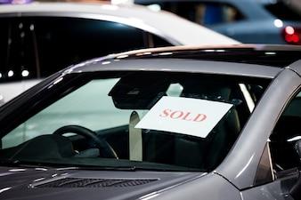 Kaufender aufkleber des selektiven fokus des autos im parken am ausstellungsraum
