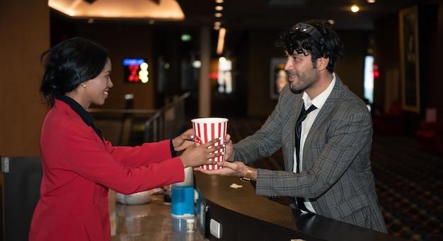 Kaufender popcornsnack des jungen mannes an der theaterkasse.