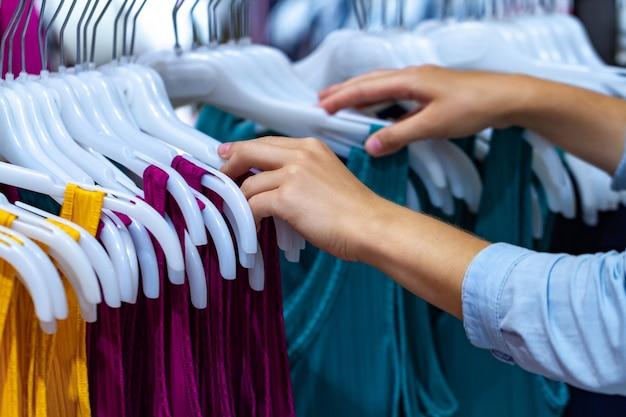 Kaufender stoff auf gebrauchtmarkt im einkaufszentrum. umsatz und rabatt. einkaufszentrum der frau in mode, neue kleidung für garderobenaktualisierung wählend