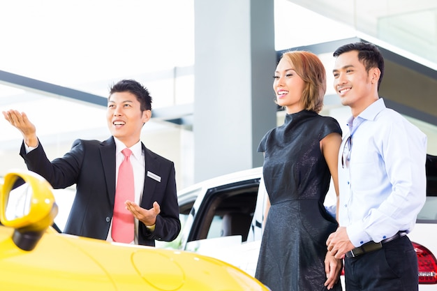 Kaufendes auto der asiatischen paare in der verkaufsstelle