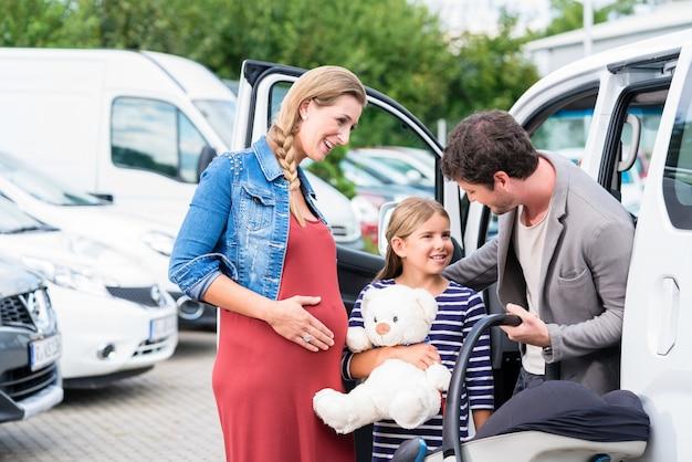 Kaufendes auto der familie, mutter, vater und kind am autohaus
