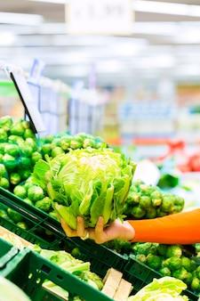 Kaufendes gemüse der frau im supermarkt