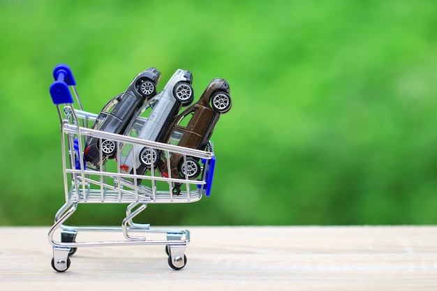 Kaufendes neues autokonzept, miniaturautomodell im warenkorb auf natur