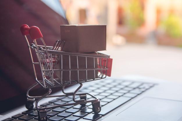 Kaufendes on-line-konzept - einkaufen mit zahlung durch kreditkarte einkaufswagen auf einem laptop