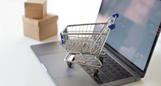 Kaufendes on-line-konzept: einkaufswagen auf laptop
