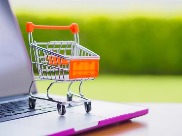 Kaufendes on-line-konzept: minieinkaufswagen auf laptop.